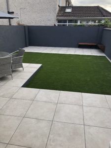 Outdoor porcelain patio area surrounded by artificial grass