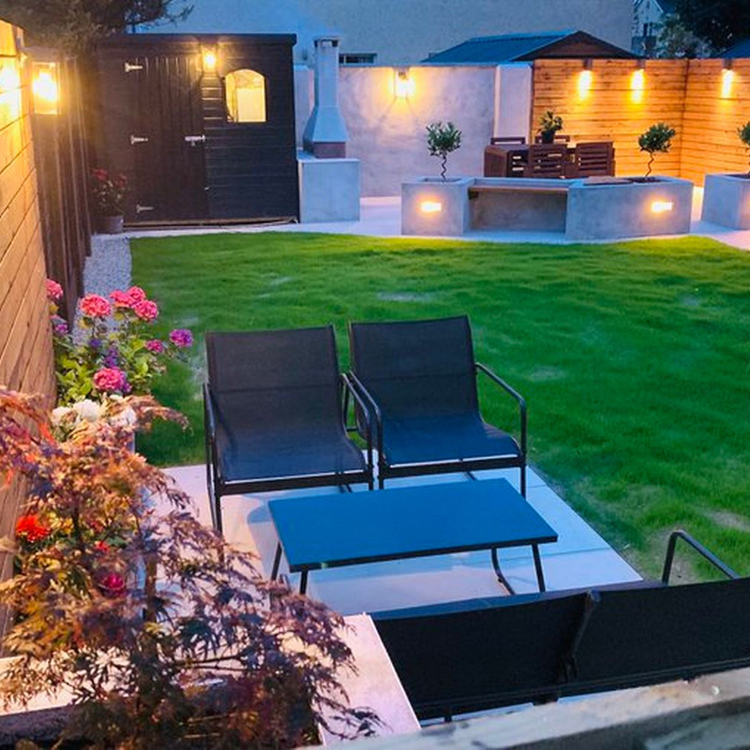 Back garden that contains 20mm porcelain paving at night