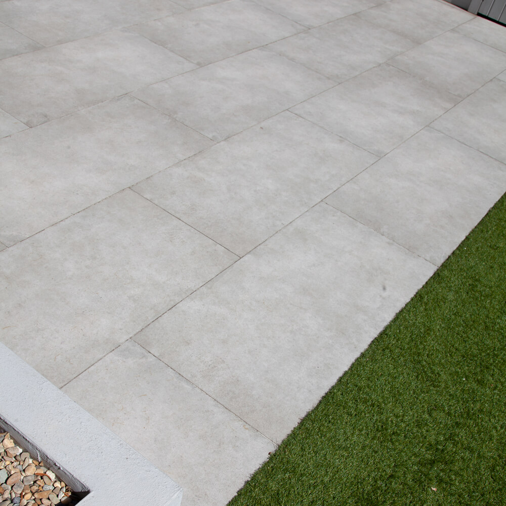 Patio created from outdoor porcelain with artificial grass