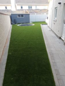 Garden with natural stone paving and artificial grass